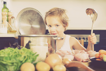 Little girl cooking soup  at  kitchen