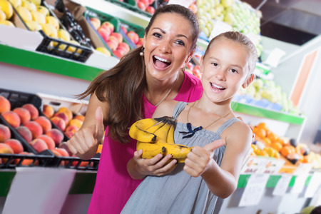 Excited young woman with girl looking satisfied and holding thumbs up  in fruit store