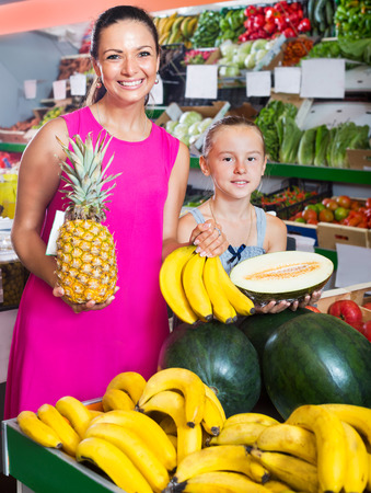 Positive mother with girl picking different fruits in the supermarket. Focus on woman