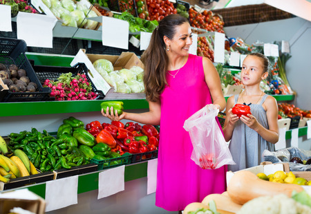 Smiling mother with girl buying fresh peppers at a vegetable section in shop. Focus on woman Zdjęcie Seryjne