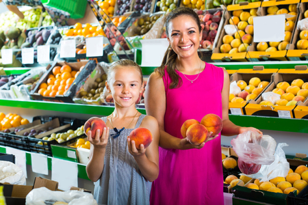 portrait of cheerful smiling  mother with little daughter taking peaches on fruit market Zdjęcie Seryjne