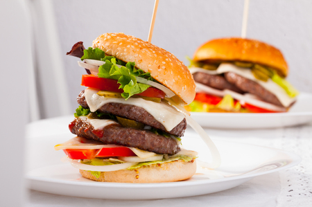 Two tasty double-decker  grilled burger with beef, tomato, cheese, cucumber and lettuce