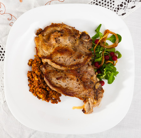 Top view of baked pork shank with lentils garnishing with green corn salad and red currant berries Stock fotó