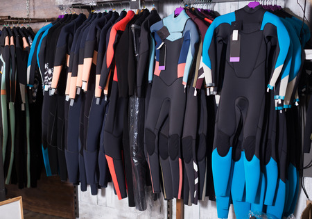 Image of colorful wetsuit hanging in the modern european store for surfing Stock Photo