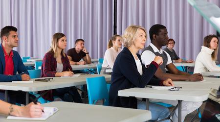 Grupo multinacional de estudiantes adultos escuchando profesor en el aula