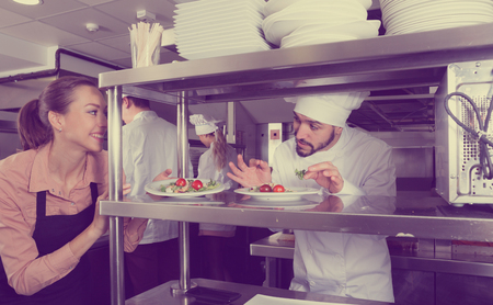 Head chef checking dishes in kitchen of restaurant before serving guests Фото со стока - 106441990