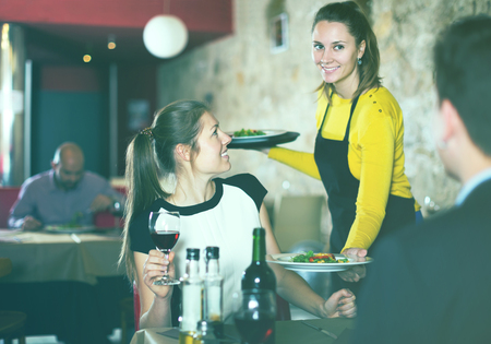 Polite waitress bringing ordered dishes to young couple at restaurant. Focus on sitting woman Фото со стока - 106441992