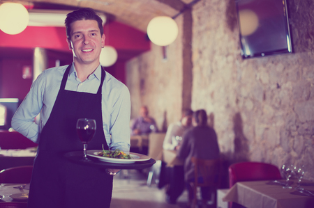 Smiling waiter holding tray at restaurant with customers his behind