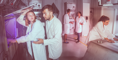 females and males are searching for a solution to a puzzle in a quest room laboratory