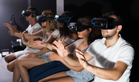 females and males try modern virtual reality glasses in a room