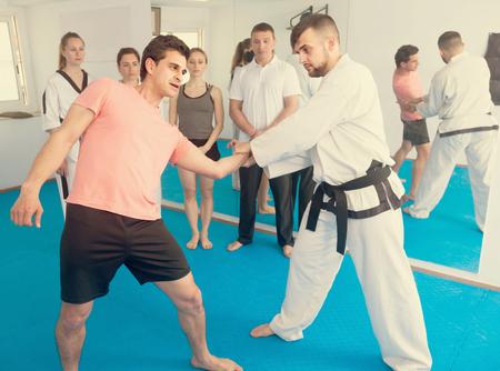 happy spanish man training new taekwondo holds with adults during class Archivio Fotografico