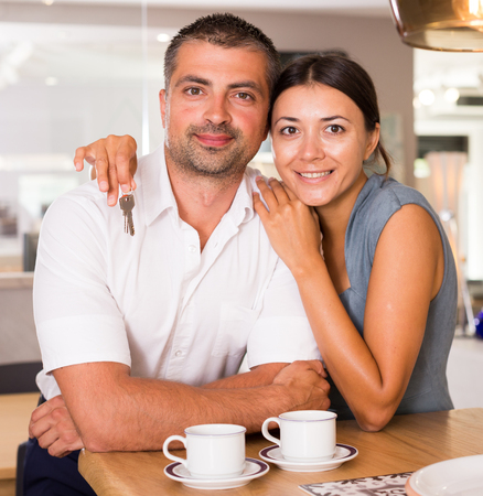 Portrait of happy young couple in kitchen of their new house, woman holding keys