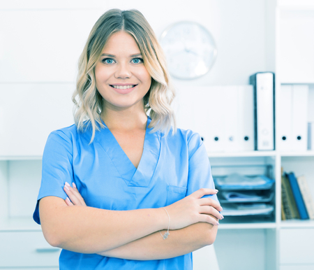 A friendly girl in doctor's uniform smiling at the office
