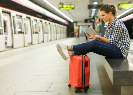 A smiling female traveler waiting for the train at a metro station sitting on the stone bench with legs stretched out on the suitcase Banco de Imagens