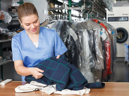 A young happy female worker of laundry inspecting clothes after dry cleaning, satisfied with result