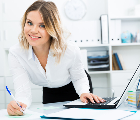 Attentive girl writes something on a sheet of paper in modern office Stock Photo