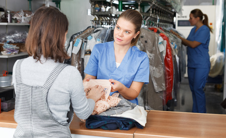 Young woman working with client in modern laundry, receiving clothing for dry cleaning