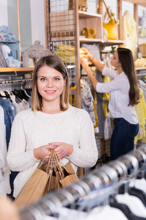 Smiling young woman  carrying  paper bags with purchases  in fashion store