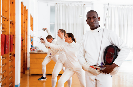 Active african american cheerful  smiling male fencer in uniform standing with mask and foil at fencing room Stock Photo