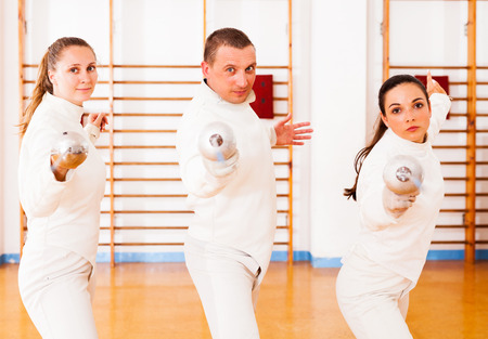 Man and women fencers practicing movements together at fencing workout 版權商用圖片