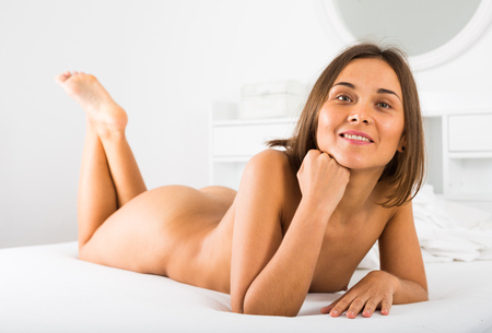 Smiling girl lying leisurely in bed in morning