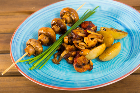 Tasty mix of roasted mushrooms with baked potatoes decorated with chives 스톡 콘텐츠