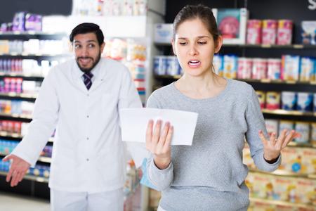 Retrato de cliente mujer indignada con medicamentos en farmacia Foto de archivo