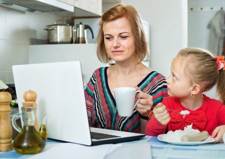 Smiling positive woman sitting with laptop in the kitchen and eating together with her cheerful daughter 免版税图像 - 106577497