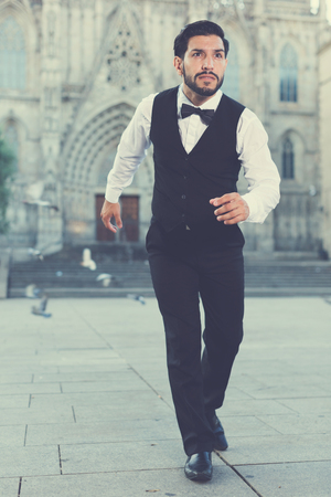 Handsome bearded hurrying man running along old town street