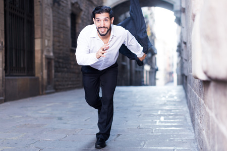 Handsome emotional man in formalwear running along ancient street