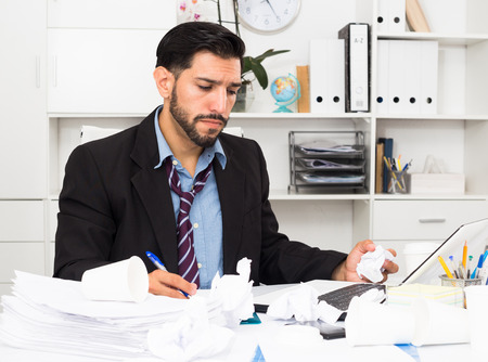 Man employee is indignant because he is having issues with project in office. Stockfoto