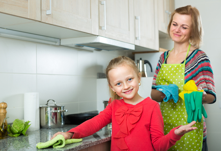 Portrait of little girl helping her joyful mom tidy up at home kitchen Archivio Fotografico