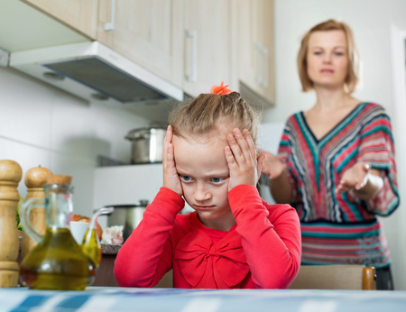 Crisis of motherhood: ordinary young woman preaching little sad daughter