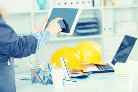 Mujer de negocios sosteniendo y usando la tableta en el lugar de trabajo en la oficina