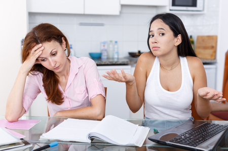 Mother upset because her daughter is not studying well, scene in kitchen Stock Photo