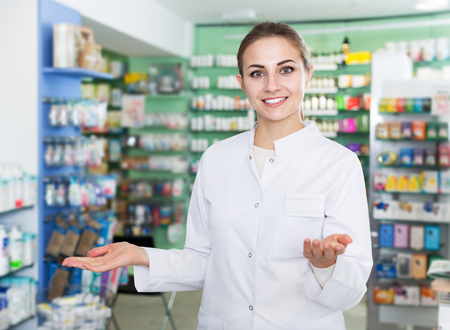 Portrait of positive woman specialist who is standing near shelves in drugstore