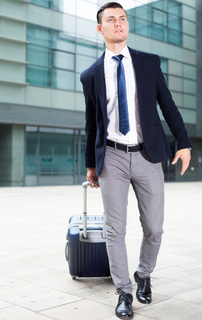 Adult man in suit with suitcase is staying near the building of airport.