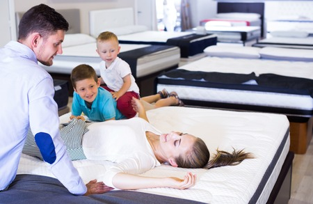 Happy woman with her family lying on back on mattress in store in search of right Stock fotó