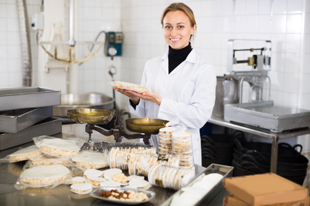 Positive woman standing with box of turron in production workshop