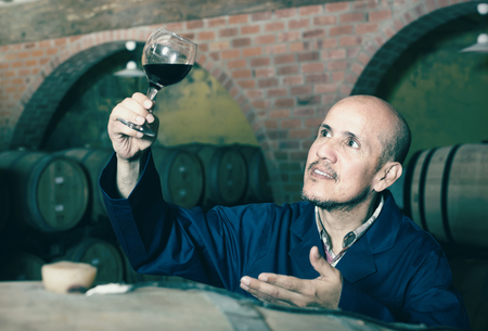 smiling mature winemaker in working coat looking at glass of wine in cellar 免版税图像 - 106734928