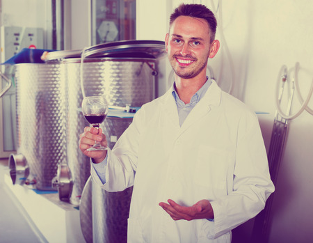 winery worker wearing white coat holding glass of wine in fermenting section 免版税图像