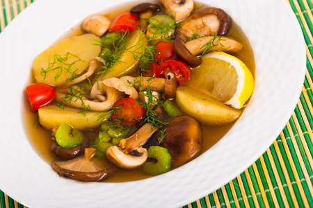 Rustic pottage cooked with mushrooms and vegetables served with slice of lemon