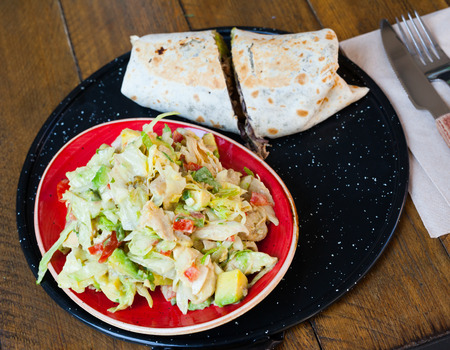 Mexican cuisine. Chicken salad with avocado and burrito with tuna Imagens