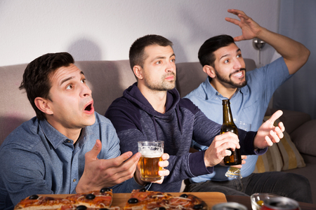 Exalted active friends watching tv together at home, enjoying beer and pizza at home Фото со стока