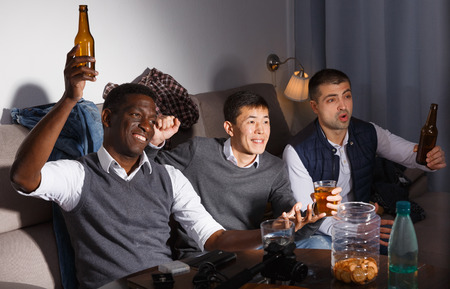 Exalted male friends watching tv together at home, enjoying beer at home