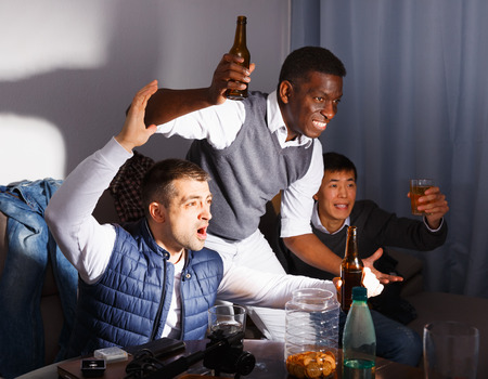 Exalted male friends watching tv together at home, enjoying beer in home interior late at night