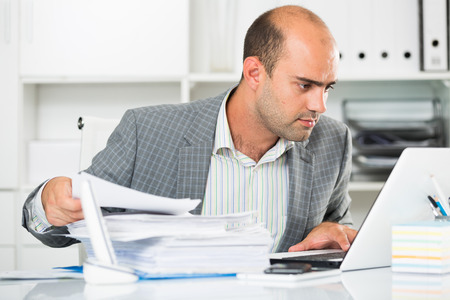 Portrait of male worker in the office sitting at the table with documents