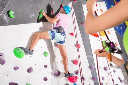 Homme sportif habillé en tenue d'escalade dans la salle de sport de bloc Banque d'images