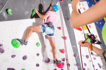 Sporty man dressed in rock climbing outfit training in bouldering gym Imagens