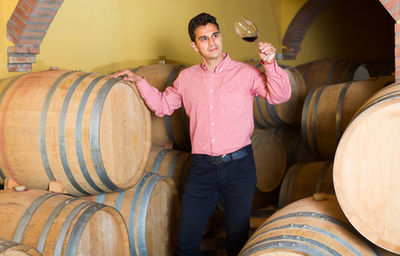 Smiling male owner of winery standing with wine in cellar
